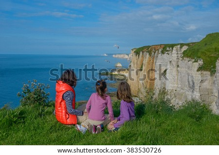 Mother and kids looking at beautiful sea view sitting on rocks, family hiking on vacation in France, Etretat  - stock photo