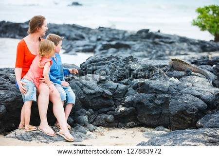 Mother and kids looking at endemic marine iguana at Galapagos islands - stock photo