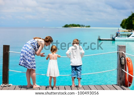 Mother and kids on wooden dock enjoying ocean view - stock photo