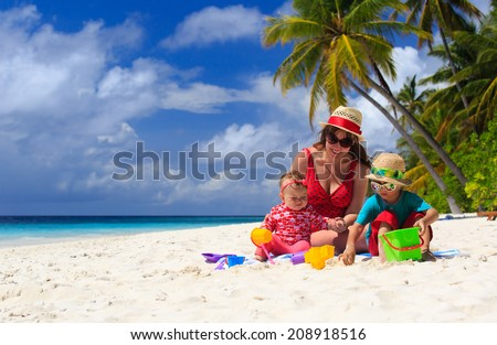 mother and kids playing on tropical sand beach - stock photo