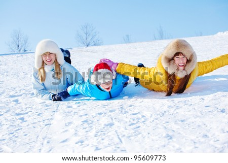 Mother and kids sliding down the snowy hill - stock photo