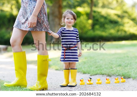 Mother and little adorable daughter in yellow rubber boots, family look, in summer park - stock photo