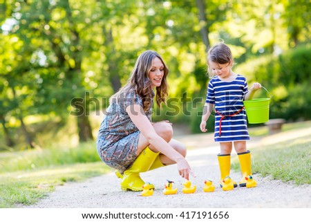 Mother and little adorable daughter in yellow rubber boots, family look. Woman and little kid girl playing with duck toys in summer park - stock photo