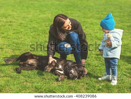 mother and little child plays with a dog on the grass, Cane Corso - stock photo