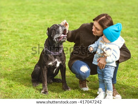 mother and little child plays with a dog on the grass, Cane Corso