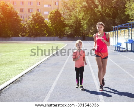 Mother and little daughter are doing exercise in the stadium. Family doing fitness at the stadium. Healthy family concept - stock photo