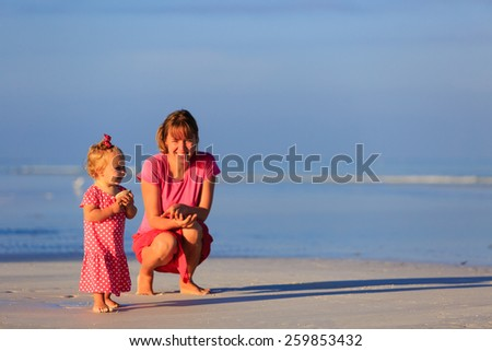 mother and little daughter collecting shells on summer beach