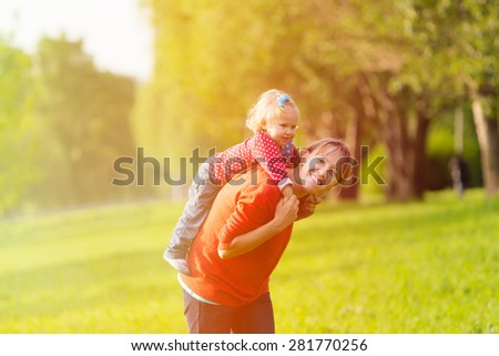 mother and little daughter having fun outdoors in summer - stock photo