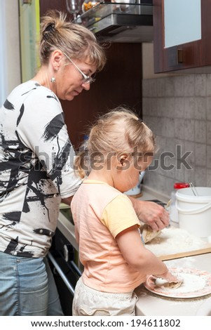 Mother and little daughter kneading dough together in kitchen - stock photo