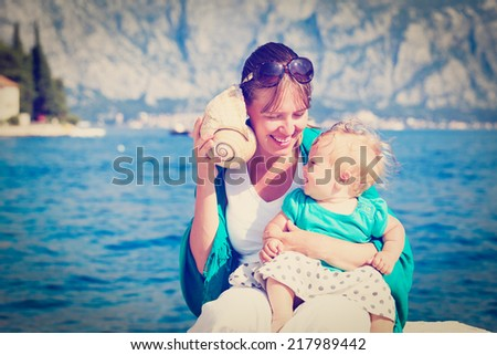 mother and little daughter listening seashell on vacation - stock photo