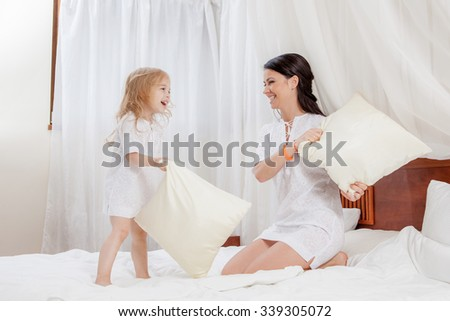mother and little daughter on bed