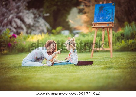 Mother and little daughter paint together in a park