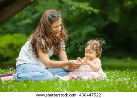 Mother and little daughter playing in the park
