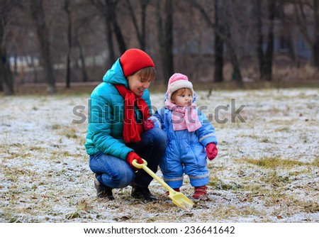 mother and little daughter playing in winter park - stock photo