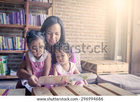 Mother and little daughter reading book together in library,soft color filter