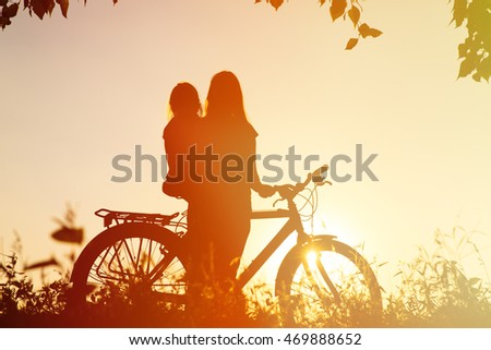 mother and little daughter riding bike at sunset