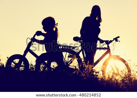 mother and little daughter riding bikes at sunset