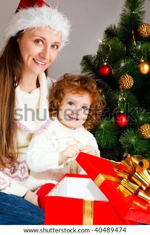 Mother and little daughter sit near Christmas tree with a present box