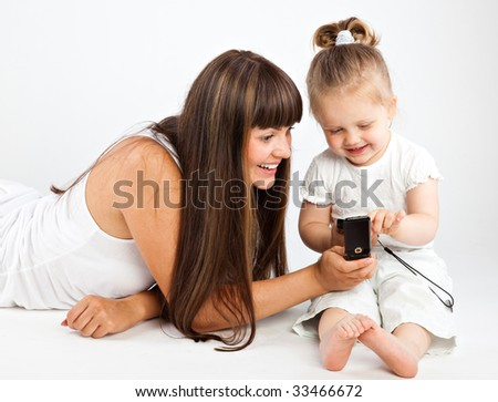 Mother  and little daughter speaking by phone. Gray background