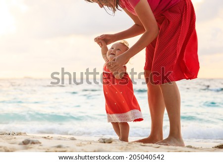 mother and little daughter walking on sand beach - stock photo