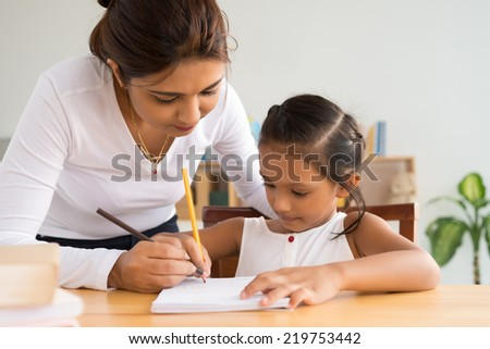 Mother and little daughter writing together - stock photo