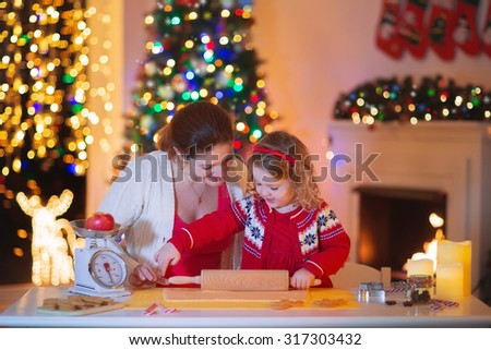 Mother and little girl baking Christmas pastry. Children bake gingerbread. Toddler child preparing cookie for family dinner on Xmas eve. Decorated kitchen or dining room with fireplace, tree, candles - stock photo