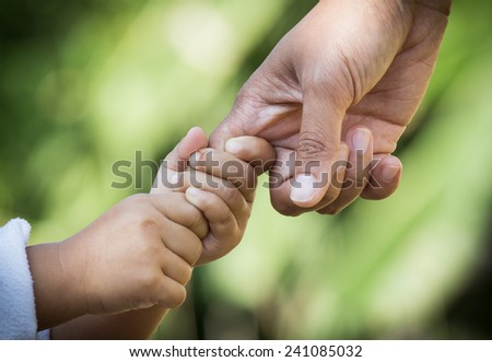 Mother and little girl holding hands together - stock photo