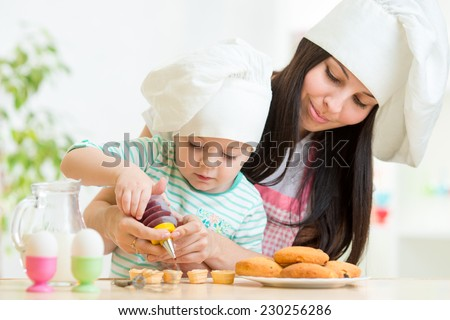 Mother and little girl making cookies together at kitchen - stock photo