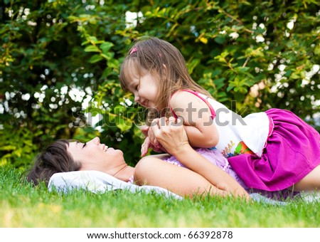Mother and little girl on meadow - stock photo