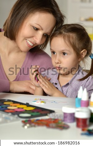 Mother and little girl painting at home