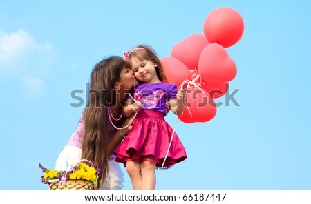 Mother and little girl with red ballons and teddy bear - stock photo