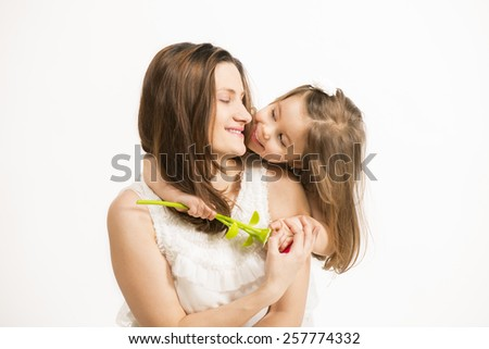 Mother and little lovely daughter. Beautiful little girl embracing her mother on white background. Happy family concept. Mothers day. - stock photo