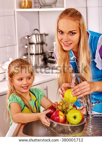 Mother and little ones kid is washing fruit at kitchen. - stock photo
