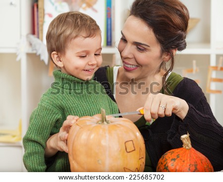 Mother and little son carving pumpkins for Halloween - stock photo