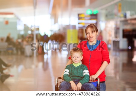 mother and little son on trolley in the airport