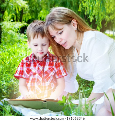 Mother and Little Son reading a magic book, sitting on green grass in a park  - stock photo