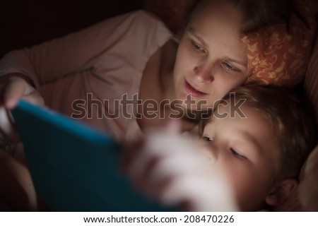 Mother and little son watching video or playing on touchpad lying in bed at night
