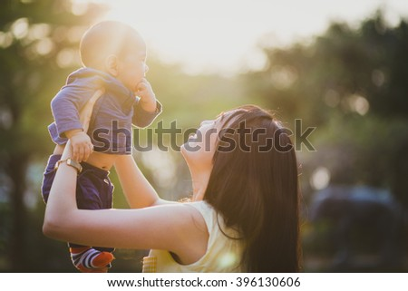 Mother and lovely son at sunny field with intentional sun glare. Happy family concept.