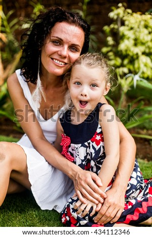 mother and preteen daughter summer portrait in the green beautiful park  - stock photo