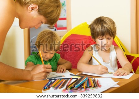 Mother and siblings playing with pencils in home interior