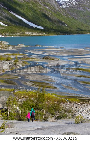 mother and sisters hiking on the lake with  mountains and valley the glacier Nigardsbreen at the background