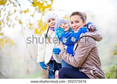 mother and sisters in autumn park