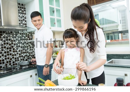Mother and son are helping to make a salad in the kitchen - stock photo