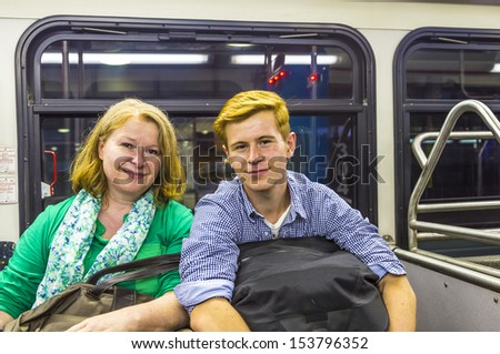 mother and son at the airport bus after arrival with baggage by night - stock photo