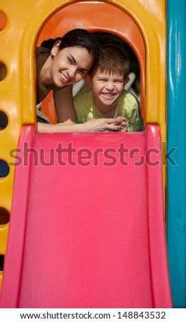 Mother and son at top of slide at playground, smiling, looking at camera. - stock photo