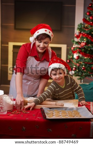 Mother and son baking cake together for christmas, smiling.? - stock photo