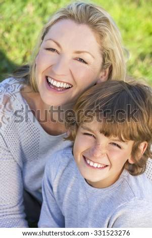 Mother and son, boy child and woman, laughing together, sitting outside in summer sunshine - stock photo