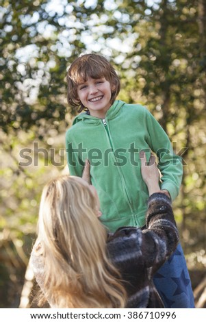 Mother and son, boy child and woman, playing & laughing together outside in summer sunshine
