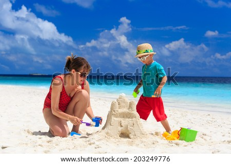 mother and son building sand castle on tropical sand beach