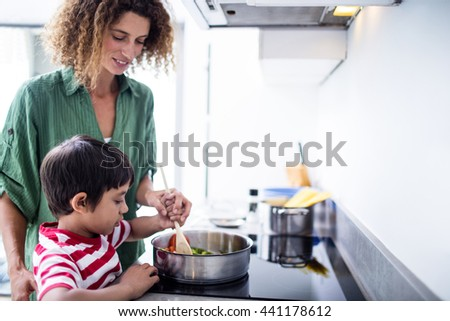 Mother and son cooking in kitchen at home - stock photo